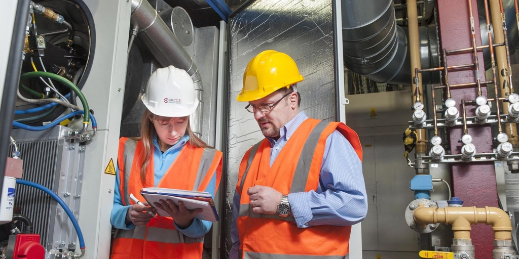 a man and a woman look at a notepad, stood next to a piece of research equipment, both are wearing safety hats and hi-vis jackets