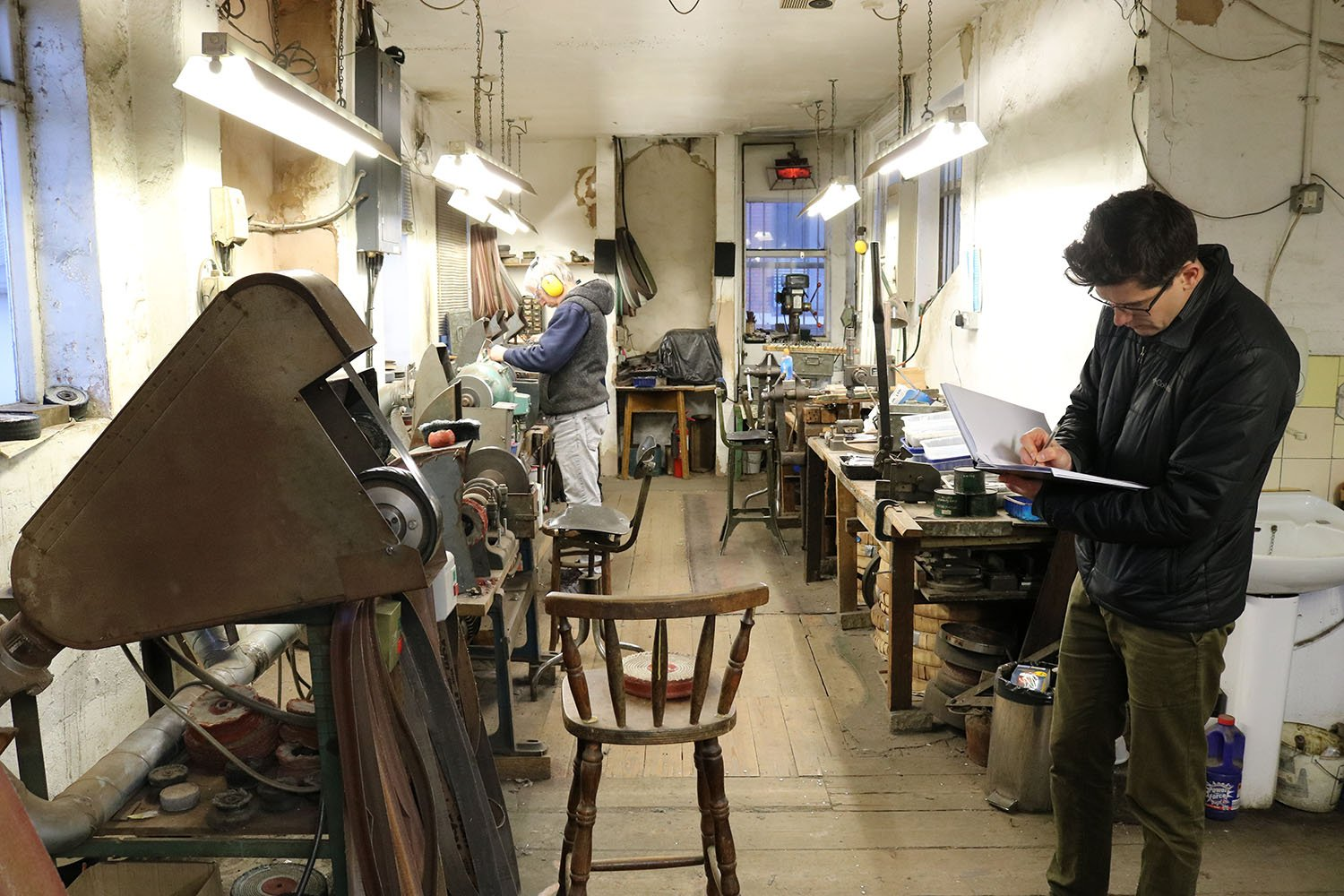 a man writes on a clipboard in the foreground of a metalwork workshop, in the background a man in ear defenders works on equipment