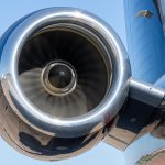 Rolls Royce aircraft engine in motion on a Gulfstream private jet set against a blue sky.